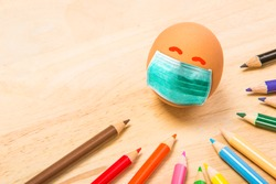 Color pencils and an egg with green medical or hygienic mask  on wood background, Preparing for protection children from Covic 19 or Corona virus pestilence on Easter day concept