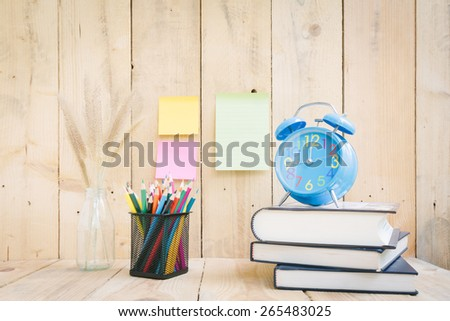 Color pencils and book with clock on wooden background - Vintage effect style pictures
