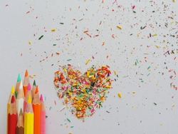 Color pencils and color dust heart-shaped on white paper.