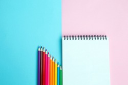 Color pencils and notebook on color background. School and office accessories. school concept. flat lay top view copy space