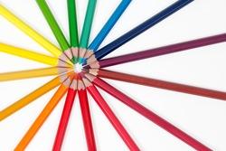 color pencils arranged in a circle top left on white background, top view