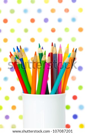 Color pencils arranged in a white cup and shot against a colorful polka dot background. Back to school. Cheerful and bright.