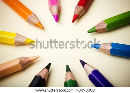 Color pencils in arrange in color wheel colors on paper background