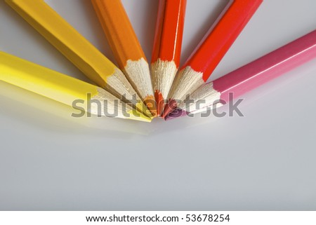 Color pencils in arrange in color wheel colors on white background - stock photo