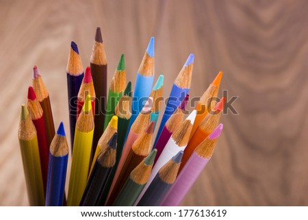 Color pencils in arrange in color wheel colors on wood background