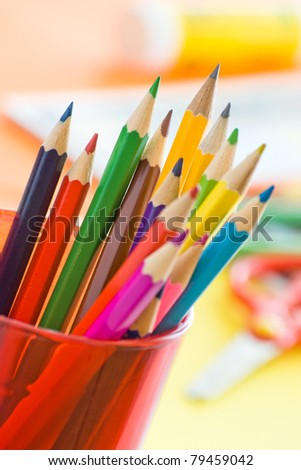 color pencils in glass on desk with shallow depth of field