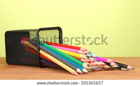 Color pencils in glass on wooden table on green background