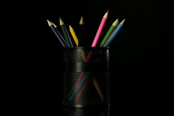 Color pencils in glass with back background