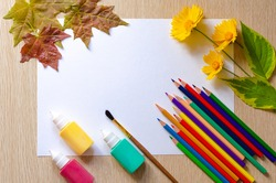 Color pencils, paint tubes, canvas for painting and autumn leaves on wooden desk. Back to school and art concept. Copy space. Flat lay.