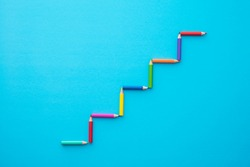 Color pencils staircase form on blue background with copy space. Business, creative idea, kids art education and development concept.