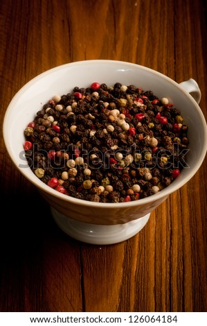 color pepper in a porcelain dish - on a wooden background