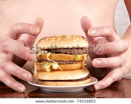 Color photo of a fat man with a hamburger in his hand