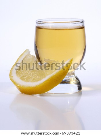 Color photo of a glass cup with tequila and lemon #69393421
