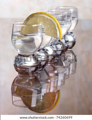 Color photo of a glass cup with tequila and lemon