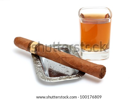 Color photo of a glass of whiskey and a big cigar