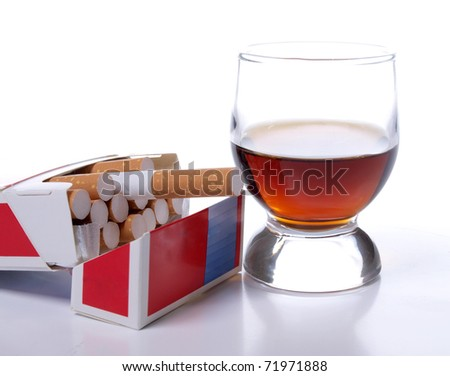 Color photo of a glass of whiskey and a pack of cigarettes
