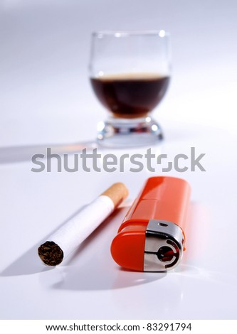 Color photo of a glass of whiskey and cigarettes
