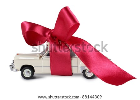 Color photo of a model car and red tape