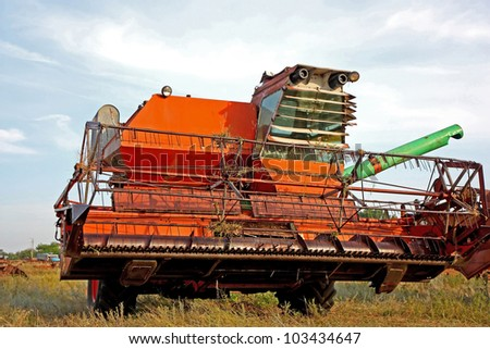 Color photo of a old combine harvester. Summer day.