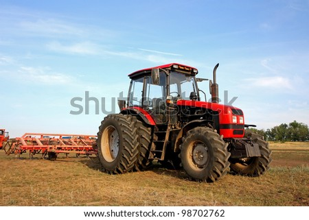 Color photo of a red tractor with a harrow