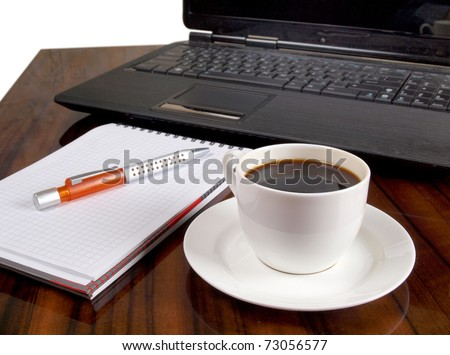Color photo of a workplace with a laptop and a cup of coffee