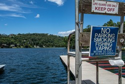 color photo of life guard stand at a lake with a dock. The lake water is int he photo with the mountains and tress in the background.