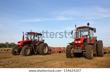 Color photo of two red tractors with a harrow