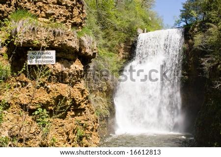 Color photograph of a No Fishing, No Swimming, and No Trespassing Sign next to the Waterfall at Apple Canyon Lake, Illinois.