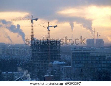 Color photograph of construction cranes on skyline
