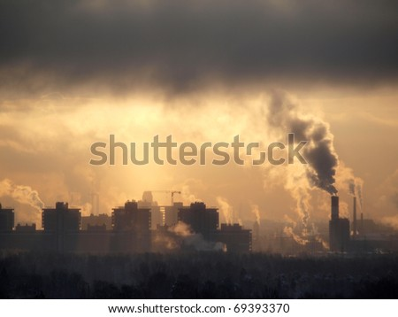Color photograph of industrial buildings at sunset