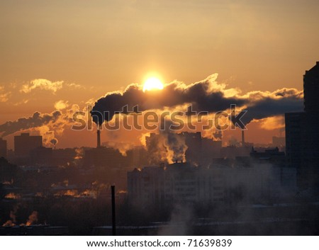 Color photograph of industrial buildings at sunset sky