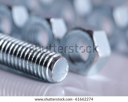 Color photograph shiny metal nuts and bolts