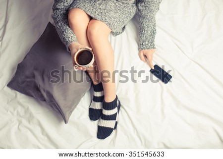 Color picture of a beautiful young woman drinking coffee at home in her bed wearing a cozy sweater while checking her phone