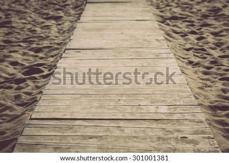 Color picture of a vintage wooden boardwalk on a sandy beach