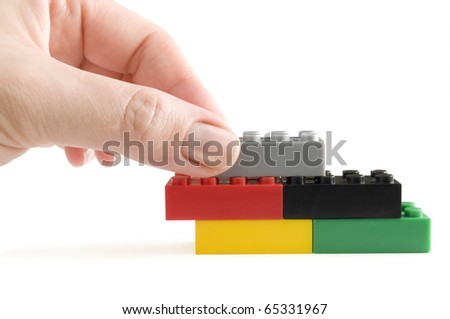 color plastic block in hand building wall isolated on white