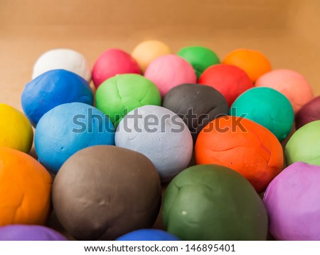 color plasticine balls on brown paper background