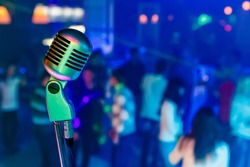 Color professional studio microphone in a night club. There are dancing people on background.
