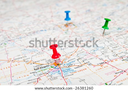 Color pushpins marking a location on a road map.