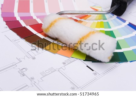 Color samples for selection and a a painter´s roll with house plan on background