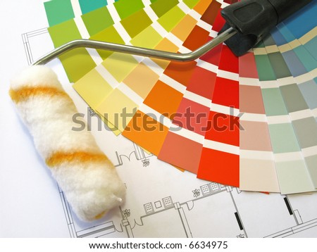 Color samples for selection and a roll with house plan on background