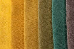 Color scheme of home interior decoration sample swaps of textured curtain fabric from golden yellow to green and grey