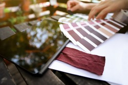 color selection meeting at a trendy fashion company - close up on inspection of red lab dye fabric sample, tablet computer and color fan in relaxed balcony surrounding