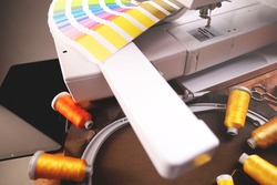 color selection process for an embroidery project with professional color fan positioned at a modern embroidery machine, different yarn samples and fabric fixed in embropidery hoop - selective focus