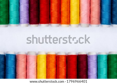Color sewing threads on white background, top view. Sewing Production. Rows Of Spools Of Thread in Different Colors. Colorful rolls of thread in the textile industry. Banner idea. Thread texture.