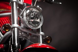 Color shot of a red motorcycle on a black background.