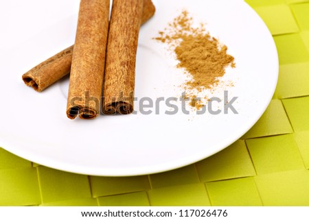 Color shot of sticks of cinnamon on a white plate