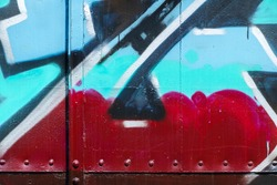 Color spray as messy graffiti on metal, part of bogie