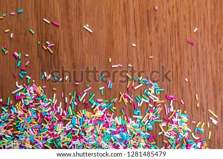 Color sprinkling. Sugar sprinkle, decoration for cake and bakery, a lot of sprinkles in a bucket on wooden background
