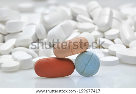 color tablets among white pills background
