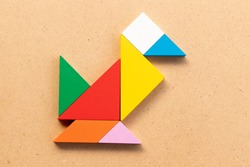 Color tangram puzzle in bird or duck shape on wood bacground